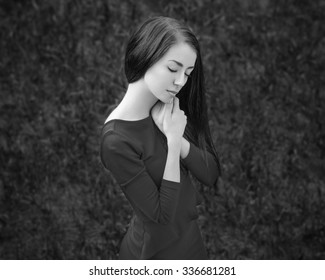 Dramatic portrait of a girl theme: portrait of a beautiful girl in the forest in a blue dress, black and white photography