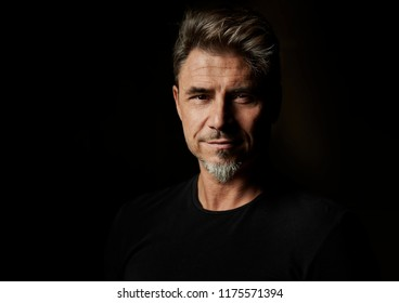 Dramatic portrait of a good looking older white guy against dark background.