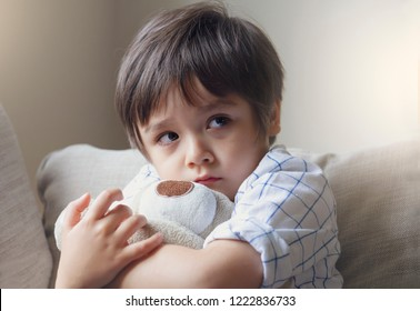 Dramatic portrait of little boy sitting on sofa and cuddling teddy bear with scared face,Unhappy Child sitting alone and looking out with worrying face,Toddler boy on corner punishment sitting.