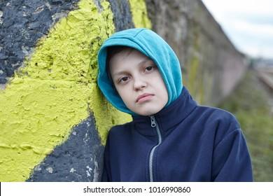dramatic portrait of a little homeless boy, city street