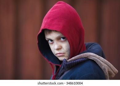dramatic portrait of a little homeless boy, poverty, city, street
