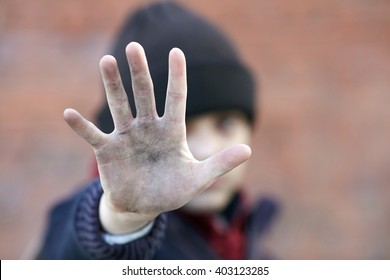 dramatic portrait of a little homeless boy, dirty hand, poverty, city, street