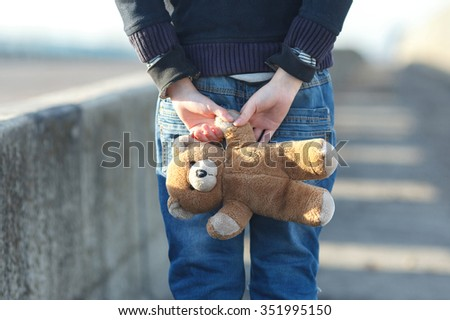 dramatic portrait of a little homeless boy holding a teddy bear, poverty, city, street