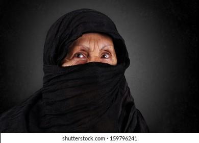 Dramatic portrait of senior muslim woman with niqab and hijab