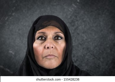Dramatic portrait of serious middle aged muslim woman with black scarf or hijab