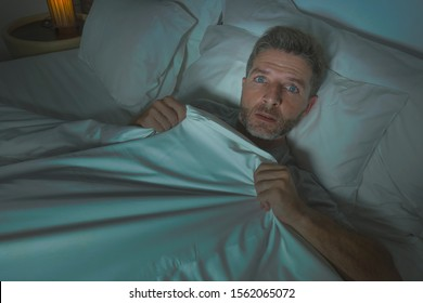dramatic portrait of stressed and scared man alone in bed awake at night in fear after having a nightmare feeling paranoid holding the blanket in funny panic face expression