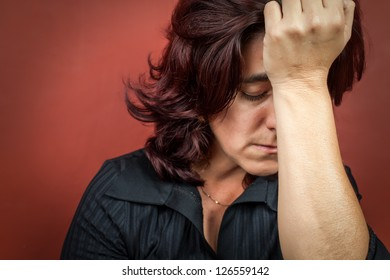 Dramatic  portrait of a woman suffering a headache or a strong depression with a dark red background