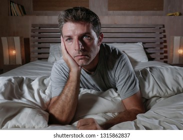 dramatic portrait of young attractive sad and depressed man lying in bed feeling worried suffering depression problem and anxiety crisis thoughtful and pensive awake at night at home bedroom