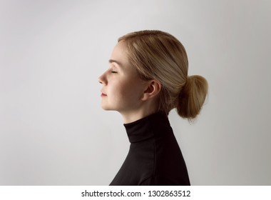 Dramatic portrait of a young beautiful girl in a black turtleneck