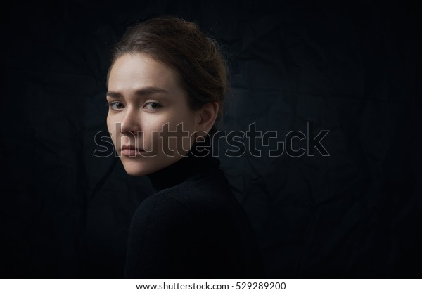 Dramatic portrait of a young beautiful girl with freckles in a black turtleneck on black background in studio