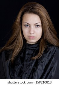 Dramatic portrait of a young lady in a black cape, may-be a young witch