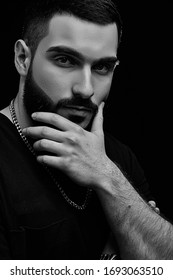 a dramatic portrait of a young serious guy, musician, singer, rapper with a beard in black clothes on a black isolated background. he is thinking carefully about something.
