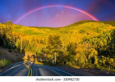 Dramatic rainbow over the Santa Fe Ski Basin highlighting beautiful aspens and pine trees