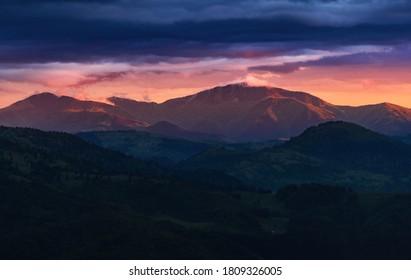 Dramatic red sunset light above Carpathian mountains. Dusk mountain landscape.