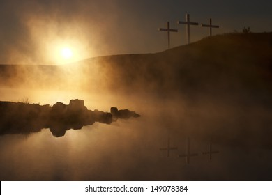 Dramatic religious photo illustration of Easter Sunday Morning reflecting a prayerful moment as a warm sun rises over a foggy lake, and three crosses on a hill reflect in the water below.