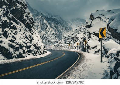 A dramatic road curve and road sign through a winter snow scene in Big Cottonwood Canyon, part of the Wasatch Mountains outside of Salt Lake City, Utah, USA.