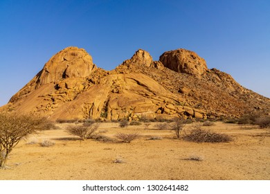 Dramatic rock formation with interesting lines and shapes and golden sunlight at dawn Spitzkoppe, Damaraland, Namib Desert, Namibia.