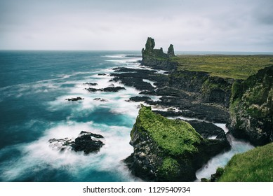 Dramatic scandinavian sea landscape with big cliffs and moody sky. Iceland outdoor travel background. Long exposure