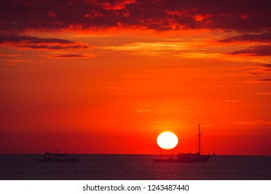 Dramatic scarlet sea sunset with boats. Summer time. Travel to Philippines. Luxury tropical vacation. Boracay paradise island. Nature background. Seascape view. Tourism concept. Water transport