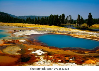 A dramatic scene of jeweled-like colored geysers in Yellowstone National Park, Wyoming that sits atop a volcanic hot spot draws tourists to it yearly.