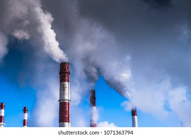Dramatic scene - the smoke coming from the pipe covering the blue sky. The concept of global warming