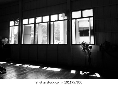 Dramatic scenery of old electric fan in Thai dancing classroom and sunlight shines through the windows in Black and White toning.