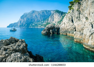 Dramatic scenic view of turquoise cove at the foot of dramatic cliffs the Mediterranean island of Capri, Italy