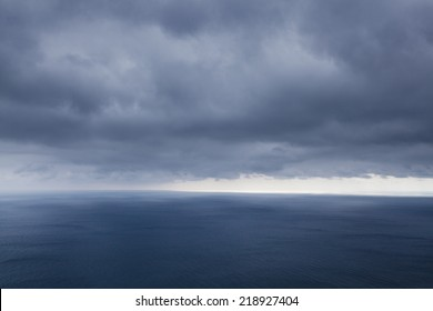 A dramatic seascape. Beams of the sun make the way through clouds and fall on the sea.