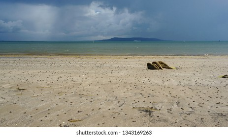 Dramatic seascape with dark blue storm clouds approaching a beautiful empty beach at low tide. Before the storm coastal landscape in Blackrock, Dublin, Ireland.