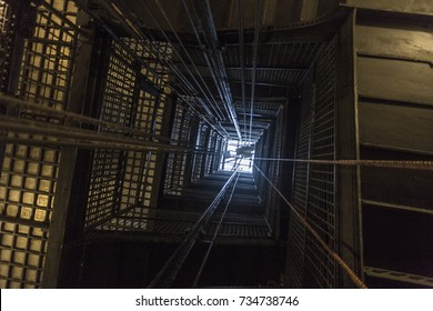 Dramatic shot looking up an elevator shaft with metal bars in vintage apartment building in dense urban area
