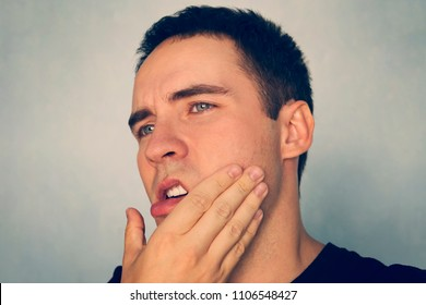 Dramatic Shot of a Man in Pain holding his Jaw. Toothache . A punch in the jaw Slap. Insult. The guy strokes his chin after shaving. stomatitis, periodontal disease, tooth extraction.