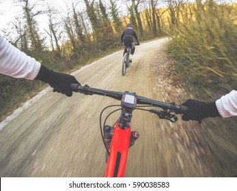 Dramatic shot of pair of young men mountain biking in a forest. POV Original point of view