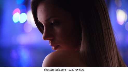 Dramatic side view close-up of beautiful woman on vibrant blurred background