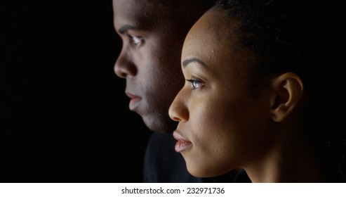 Dramatic side view of two young African American people on black background