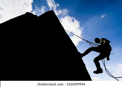 A dramatic silhouette of a climber rappeling down a rock wall. Rock climber with a rope abseil down. Mountaineer jumping down on climbing rope. Extreme adventure sport of rock climbing.