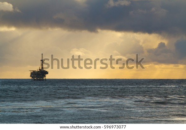 Dramatic silhouette industrial seascape of dark shadow ominous storm cloud with distant rain over ocean clearing to yellow sky to deep blue water with offshore petroleum oil derrick drilling rig pump