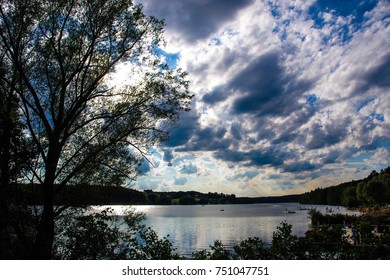 Dramatic skies reflecting on the Brombachsee lake in Germany, showing the lake's edge.