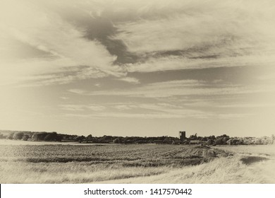 Dramatic sky and distant view of Orford Castle across fields from the footpath along the Ore Estuary, Suffolk, UK. Grainy antique vintage sepia effect.
