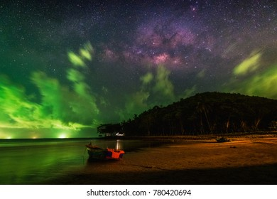 Dramatic sky with milky way, moving clouds and green light from squid catching boats, Lookalike Northern light (Aurora Boreails), and fishing boat lay down at Thungwualaen beach, Chumphon, Thailand.