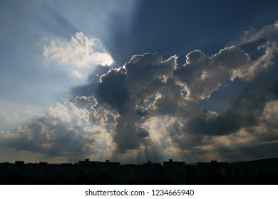 A dramatic sky with multiple god rays above a row of apartment block buildings. Taken in Košice, Slovakia