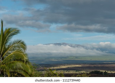 Dramatic sky over the Kohala coast on the Big Island of Hawaii at sunset with Mauna Kea peak in the background