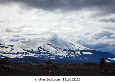 Dramatic sky over snow capped Hekla (Hecla) stratovolcano, one of Icelands most active volcanoes and popular tourist attraction in Southwestern Iceland, Scandinavia