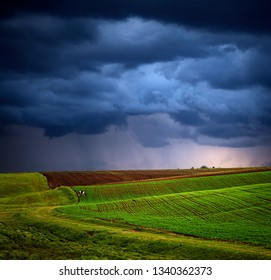 Dramatic sky over spring field, rural landscape