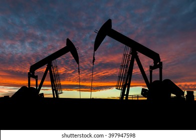 Dramatic sky over two pumpjacks in rural Alberta, Canada. These jacks can extract between 5 to 40 liters of crude oil and water emulsion at each stroke.