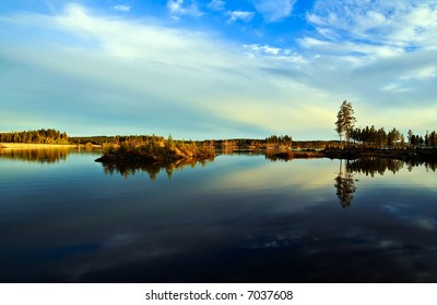 A dramatic sky reflecting in a calm northern lake