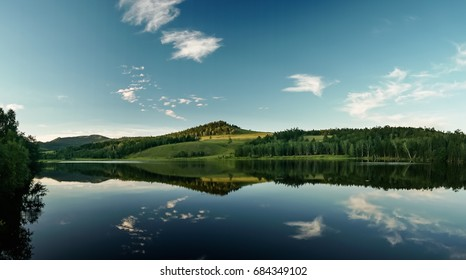 Dramatic sky reflection in calm forest lake