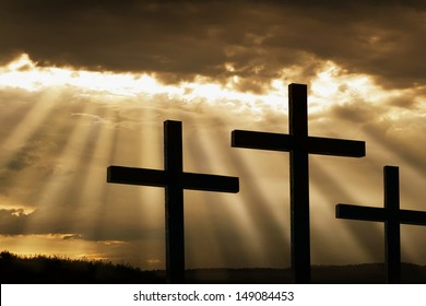 Dramatic sky silhouettes three wooden crosses with shafts of sunlight breaking through the clouds. A dramatic and inspiring religious photographic illustration for Easter or Christian beliefs