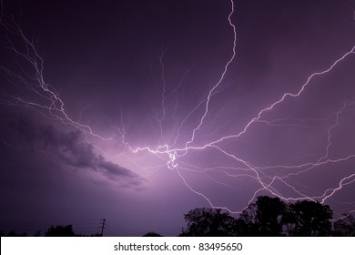 Dramatic and spectacular lightning bolts flash across the night sky illuminating storm clouds over Central Indiana in the American Midwest.