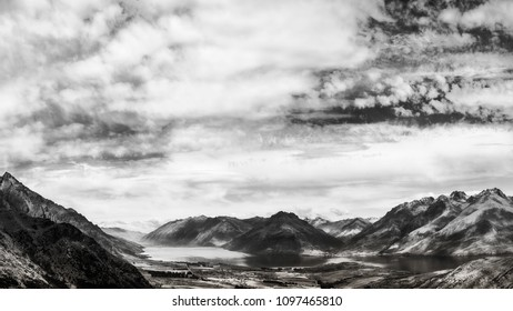 Dramatic and spectacular mountain range surrounding the Southern side of Lake Wakatipu in Black and White. View from above from above on the scenic road from Queenstown to The Remarkables Ski Area.