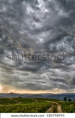 Dramatic storm scene with rain at the horizon and rural path going towards left.